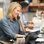 Businesswoman-Working-At-Desk-In-Warehouse-Planning-to-return-to-work